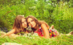 Two girls are sitting on the grass Royalty Free Stock Photo