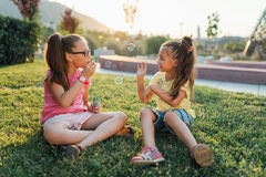Two girls are sitting on the grass and blowing bubbles Stock Photography