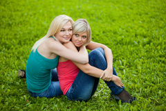 Two girls sitting on the grass, embracing Royalty Free Stock Images