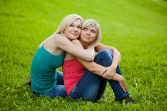 Two girls sitting on the grass, embracing Stock Photography