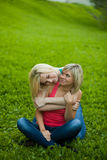Two girls sitting on the grass, embracing Stock Photos