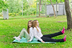 Two girls sitting on grass Stock Photo