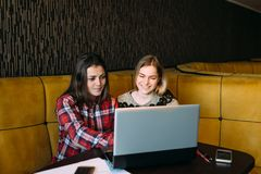 Two girls are sitting at the laptop. Two girls are sitting at a laptop in a cafe and chatting gaily Stock Image
