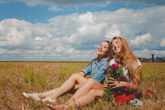 Two girls sitting on meadow with wildflowers and Royalty Free Stock Photos