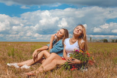 Two girls sitting on meadow with wildflowers and Royalty Free Stock Images