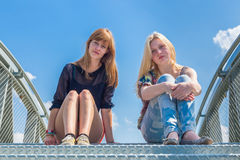 Two girls sitting on metal bridge with blue sky Royalty Free Stock Images
