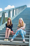 Two girls sitting on metal bridge Stock Image