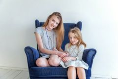 Two girls sitting on modern blue chair stock image