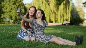 Two  girls sitting on a nature shoot selfies and having fun stock footage