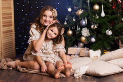 Two girls are sitting near christmas tree at home Stock Images