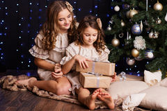 Two girls are sitting near christmas tree at home Royalty Free Stock Photo