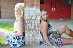 Two girls sitting next to hope. Two beautiful white Caucasian blond girls sitting next to the word hope written on a brick wall column with chalk on an outside Stock Images