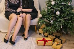 Two beautiful girls sitting next to Christmas tree opening presents. Two girls are sitting next to the tree and gifts stock photos