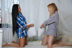 Two Girls Sitting Pillow Fight In Bed. Stock Photography