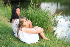 Two girls sitting by pond Stock Photo