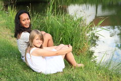 Two girls sitting by pond Stock Images