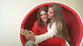 Two girls sitting in red chair, making selfies. Attractive adult girls sitting in red chair, making selfies with mobile phone and waiting for dentist visit in stock video