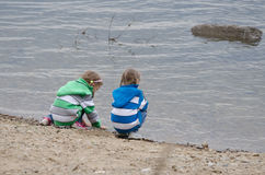 Two girls sitting on a river bank Royalty Free Stock Photography