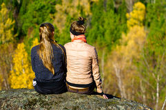 Two girls sitting on a rock. And looking at the autumn landscape Stock Image