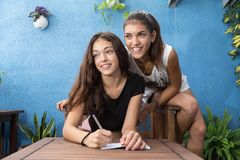 Smiling girls sitting in a wooden chair and look out of the fram. Two girls sitting on the same floor, one is ready to write but they look at something outside Royalty Free Stock Image