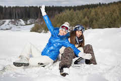 Two girls sitting on the snow and laughing. Two pretty young girls with snowboards sitting on the snow and laughing, outside Stock Images