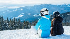 Two girls sitting on the snow looking at the mountains.  Stock Image