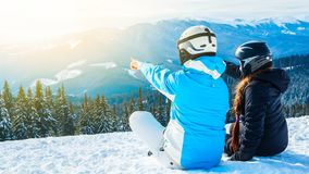 Two girls sitting on the snow looking at the mountains.  Royalty Free Stock Image