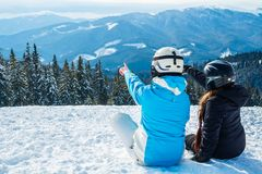 Two girls sitting on the snow looking at the mountains.  Stock Images