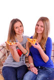 Two girls sitting on a sofa and eating pizza Royalty Free Stock Image