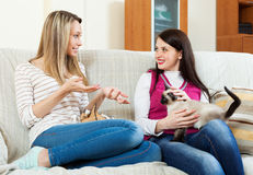 Two girls sitting on sofa and gossiping Stock Images