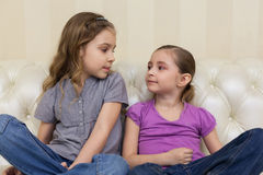 Two girls sitting on the sofa and looking at each other Stock Photo