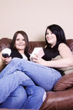 Two Girls Sitting on the Sofa Watching a Movie Royalty Free Stock Photography