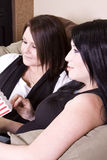Two Girls Sitting on the Sofa Watching a Movie Stock Photography