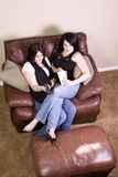 Two Girls Sitting on the Sofa Watching a Movie Royalty Free Stock Photo