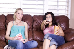 Two Girls Sitting on the Sofa Watching a Movie Royalty Free Stock Photos