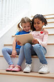 Two Girls Sitting On Staircase Using Digital Tablet Royalty Free Stock Photography