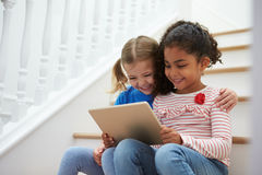 Two Girls Sitting On Staircase Using Digital Tablet Royalty Free Stock Images