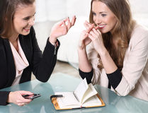 Two girls sitting at a  table. Two girls sitting at a glass table Stock Image