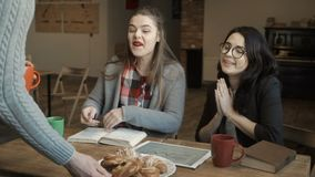 Young man invite to take a break and bring plate with baking to his colleagues. Two girls are sitting at the table and discussing some work issues, looking on stock footage