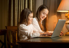 Two girls sitting at table and using laptop Stock Photography