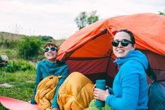 Two girls in a tent. Two girls are sitting in a tent. Girlfriends communicate in nature. Women in sleeping bags drink coffee. Friends in the campsite. Smiling stock photo