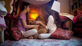 Two teenage girls sitting in tepee tent in bedroom at night. Two girls sitting in tepee tent in bedroom at night Stock Image