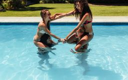 Group of women having fun in the swimming pool. Two girls sitting on their friends shoulders fighting and wrestling in swimming pool. Group of women having fun stock image