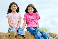 Two girls sitting on top of haybale Stock Images