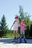 Two girls skate on roller skates in the park in the summer. Stock Photos