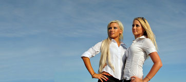 Two girls on sky background, place for text Royalty Free Stock Photos