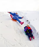 Two girls on sled through the snow to slide. Two little girls on a sled sliding down a hill on snow in winter Stock Photography