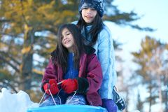 Two girls sledding Stock Photos