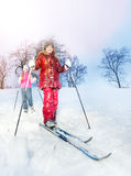 Two girls slide downhill on skies at a winter day Royalty Free Stock Images