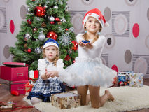 Two girls with small gifts at Christmas tree Stock Photography